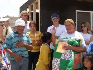 Photo of a family holding a quilt standing in front of a house under construction.