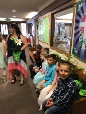 Photo of children lined up on the bench in the Narthex with lilies beside them.