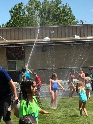 Photo of VBS children playing in a sprinkler on the lawn.