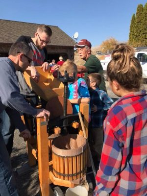 Photo of a group of parents and children around a wooden cider press outdoors.