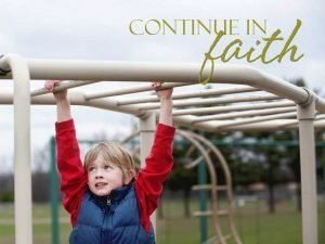 "A photo of a boy crossing the monkey bars at a playground with the words ""Continue in the Faith."""