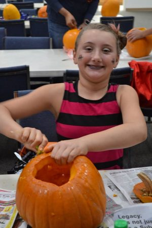 Photo of a girl carving a pumpkin.