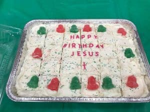 """Photo of a square cake decorated with Christmas colors and the words """"Happy Birthday Jesus."""""""