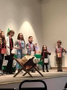 Photo of children on stage playing drums with the manger scene in the foreground