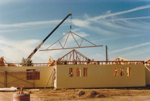 Photo of a building under construction with a crane lifting trusses to set them in place.