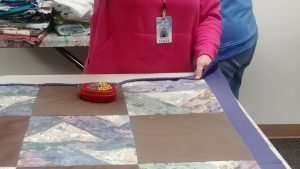 Photo of a woman putting a quilt together and folding and pinning the hem.