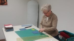 Photo of a lady cutting squares of cloth for quilting.