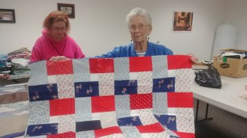 Photo of a lady holding up a red, white and blue quilt with a patriotic design.