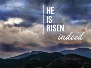 "The words, ""He is risen indeed"" over a photo of stormy sky over mountains."
