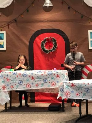 Photo of a boy and a girl on stage behind tables with various noisemakers