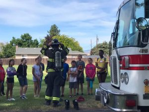 Photo of a fireman with gear in front of a firetruck talking to the children.