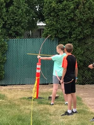 Photo of two children with the girl getting ready to shoot an arrow.