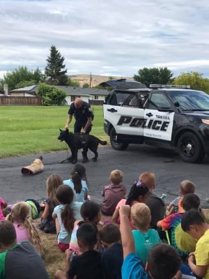 Photo of a police officer with a trained dog beside his car in front of a large group of children.