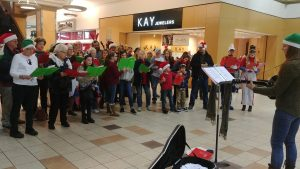 Photo of a group of more than 20 people singing carols with Kara leading the singing.