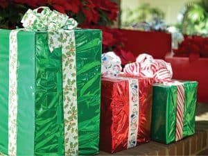 Photo of Christmas presents with brightly colored paper and wide ribbons and bows