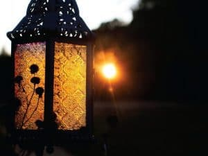 Light shining behind a lantern at dusk
