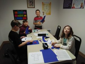 Photo of 4 students around a table working on a lesson.