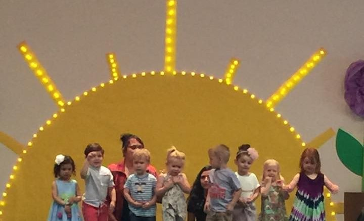 Photo of a group of 3-year-old children on the stage in front of a large yellow sun background in the Fellowship Hall.