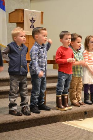 Photo of a group of small children on the step in front of the altar to sing.