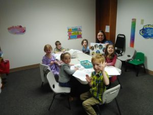 Primary children seated around a table working on projects.