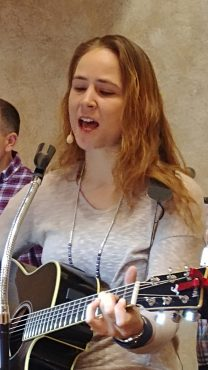Photo of a young lady with hair down past her shoulders playing the guitar and singing.