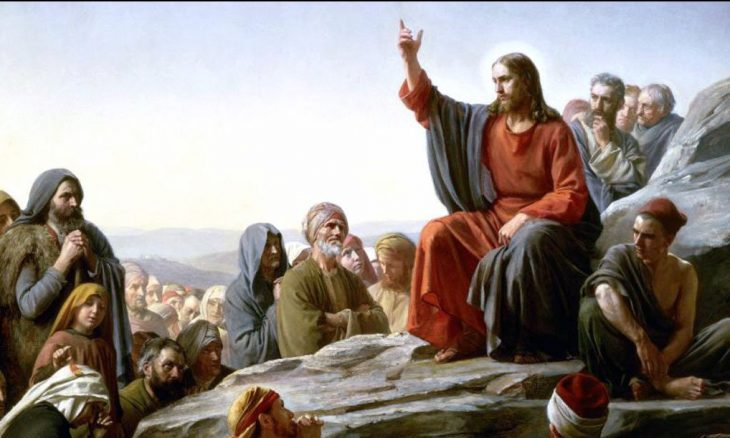 Painting of Jesus with his hand lifted up talking to a crowd, the Sermon on the Mount.