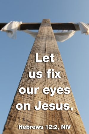"""Photo of a cross from the bottom with the words, """"Let us fix our eyes on Jesus."""""""
