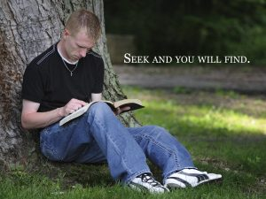 """Photo of a man sitting against a large tree reading a book with the words, """"Seek and you will find."""""""