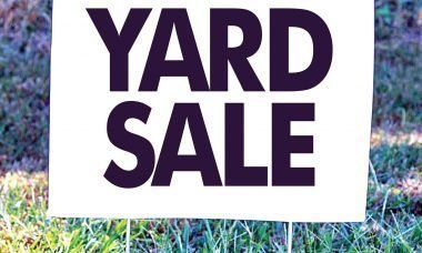 "The words, ""Yard Sale"" on a lawn sign."