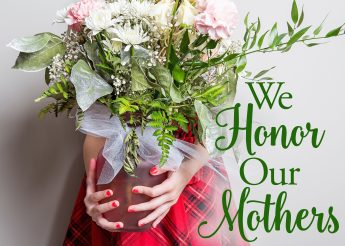"The words, ""We honor our mothers."" beside a photo of a vase of flowers in a child's hands."