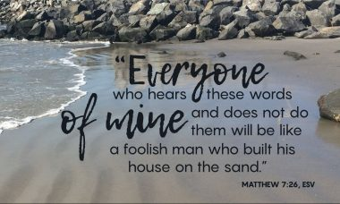 "The words, ""Everyone who hears these words of mine and does not do them, will be like the foolish man who built his house on the sand."" over a photo of a sandy beach with rocks behind."