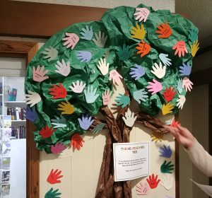 Photo of a bulletin board paper tree covered with paper hands.