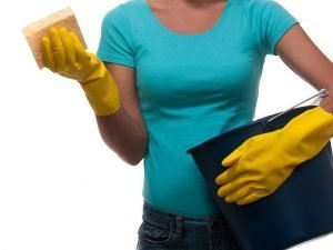 Photo of a woman wearing rubber gloves and holding a bucket.