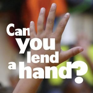 "The words, ""Can you lend a hand?"" over a photo of a hand raised."