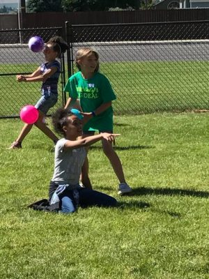 Children playing with balls on the grass.