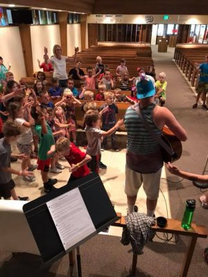 Photo from behind the VBS leader with a guitar showing the children seated in the pews.