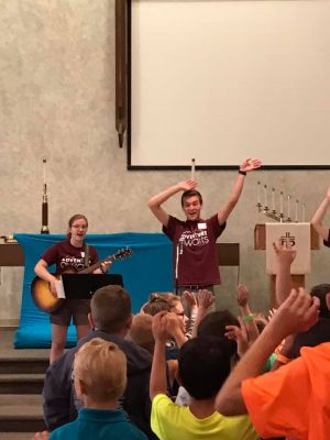 Photo of adult playing guitar and another with hands up in front of children in the Sanctuary.