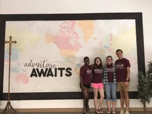 """The words, """"Adventure Awaits"""" on the bulletin board with photo of 4 young adults in VBS tee shirts."""