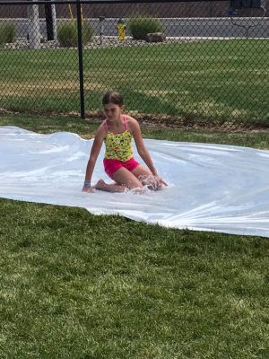 Photo of a girl sliding on her knees in water on a plastic slide.